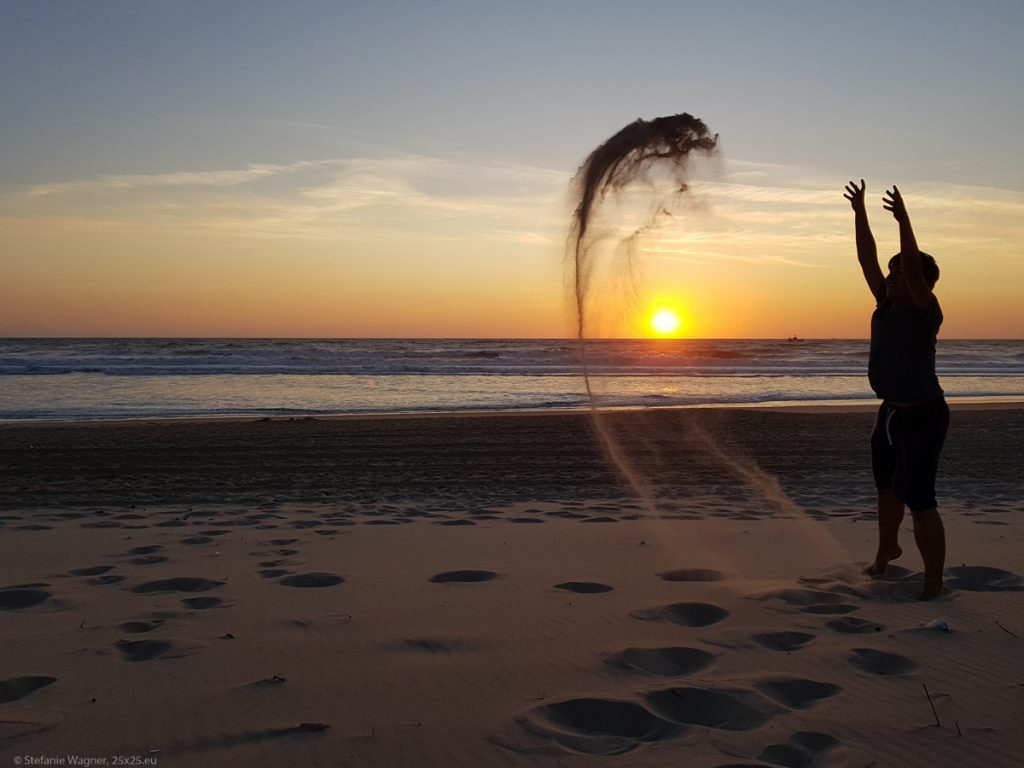Throwing sand in the air with the sunset in the background