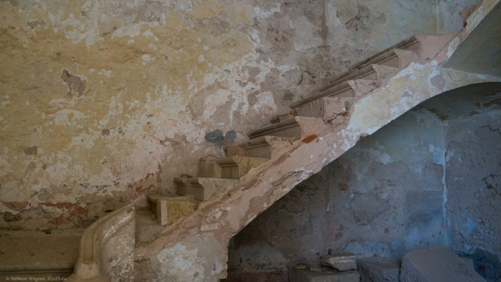 Old stairs in building with color crumbling from the walls