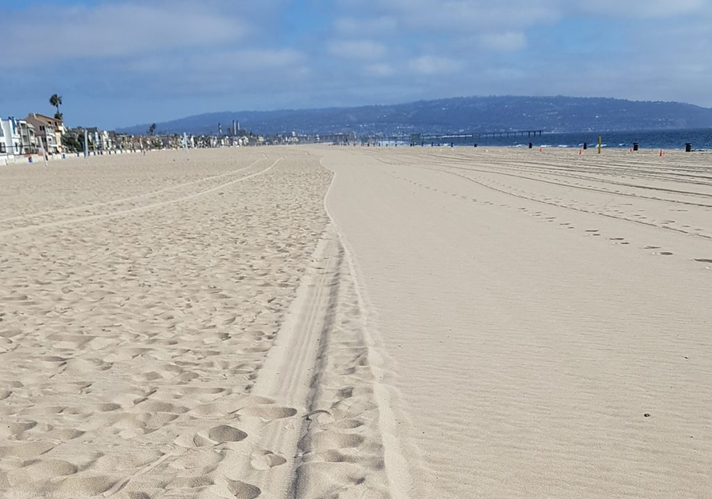 Beach - on the left side with typical footprints, on the right side smoothed by some cleaning machine