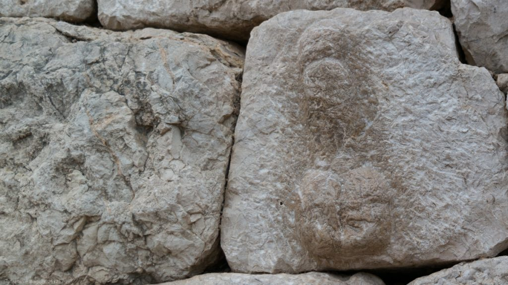 Stone in the wall with a phallus symbol carved out of it.