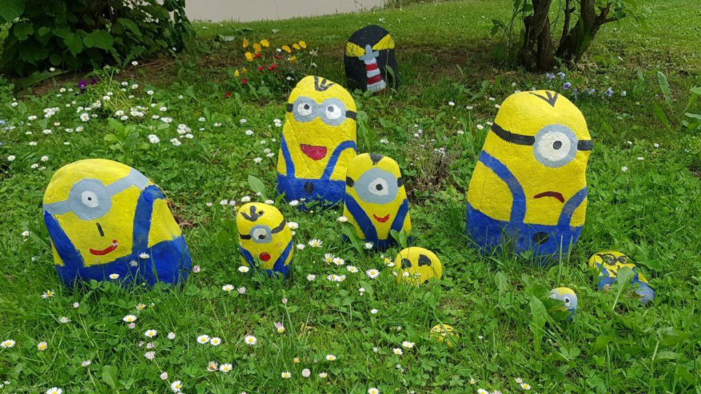 Stones painted like Minions in a front yard