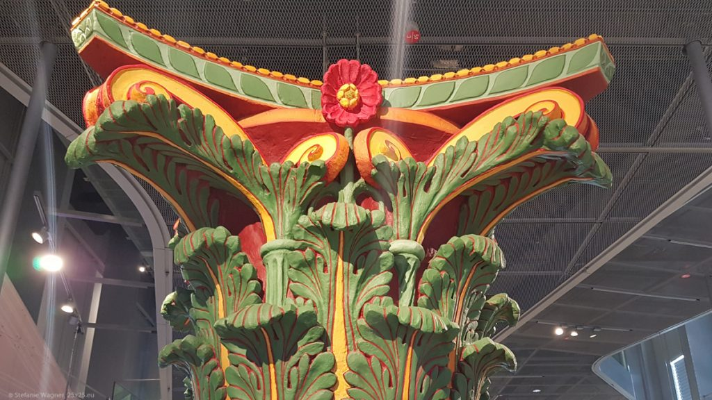The cap of a pillar painted in bright green, red, yellow, and orange.