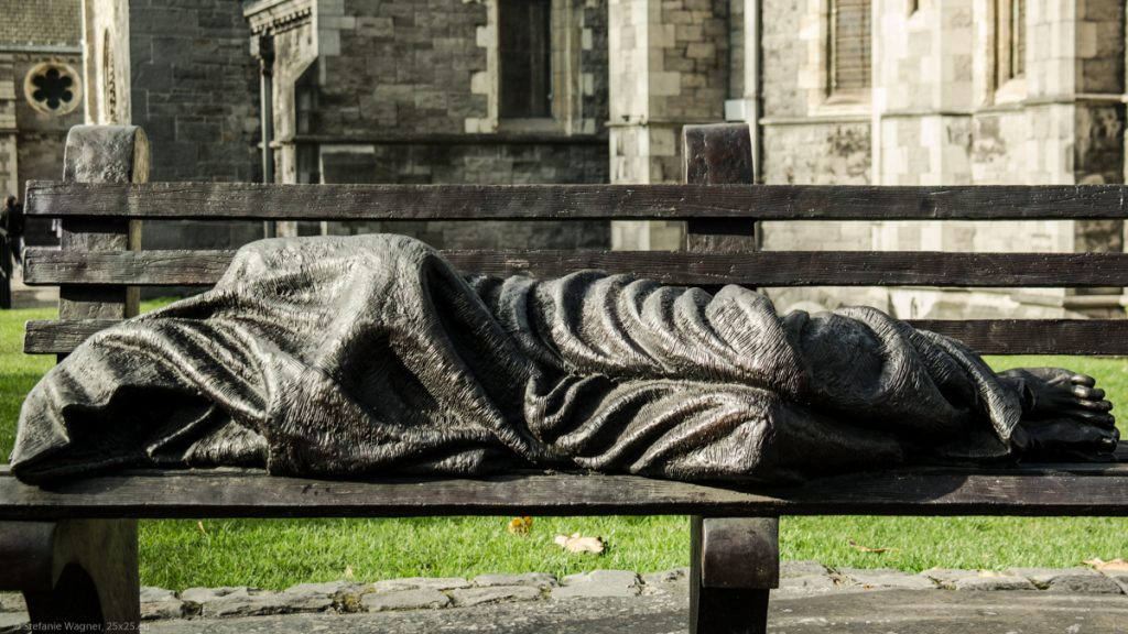 Sculpture of a homeless Jesus sleeping on a park bench in front of a church.