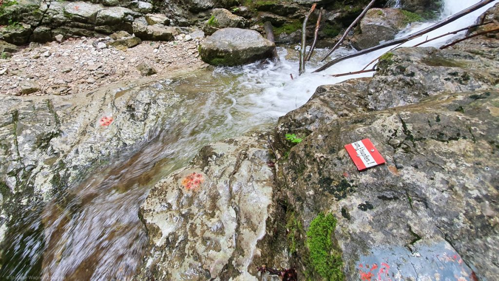 """A small stream with rocks on both sides and a small sign with the colors of the Austrian flag on one of the stones saying """"umi hupfen"""""""
