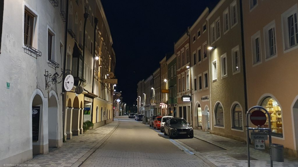 Street with colored houses to the left and the right, at night, so street lamps are on