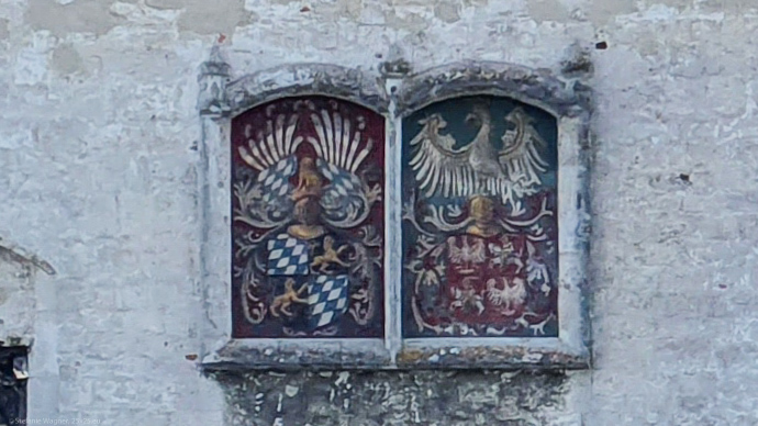 Two colorful coats of arms on a castle wall