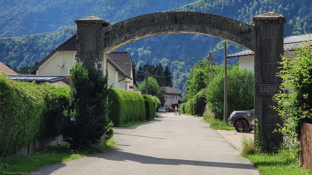 A stone arch over a street with houses in the background