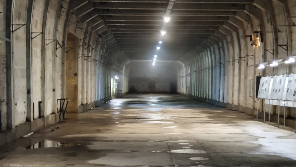 A wide tunnel, texts on display, puddles on the floor