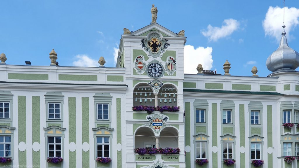 City hall with ornaments, painted in green and white, 24 bells in different sizes, inscription says city hall since 1574