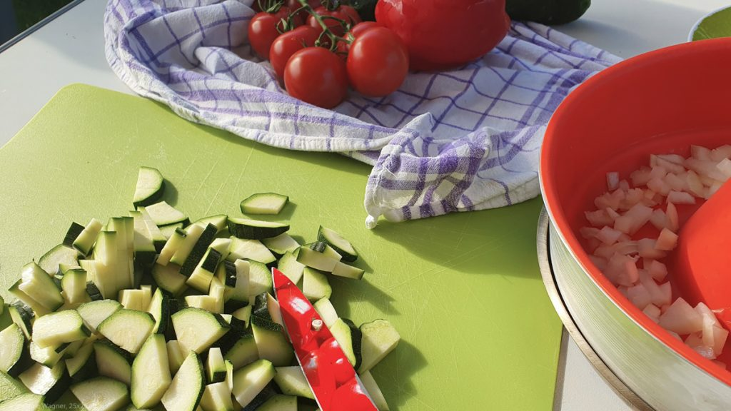 Chopped onions and zucchini, tomatoes and bell pepper in the background