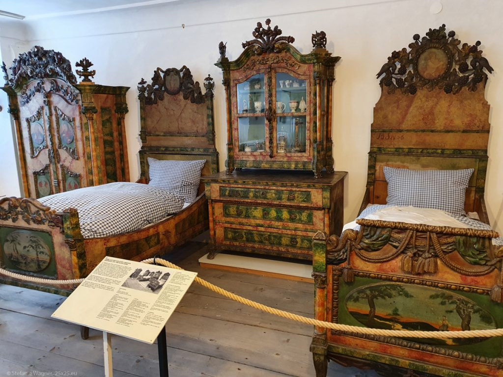 2 single beds and 2 closets made of dark wood with paintings and ornaments