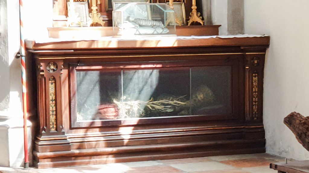 Skeleton lyining with some decoration behind glas below an altar