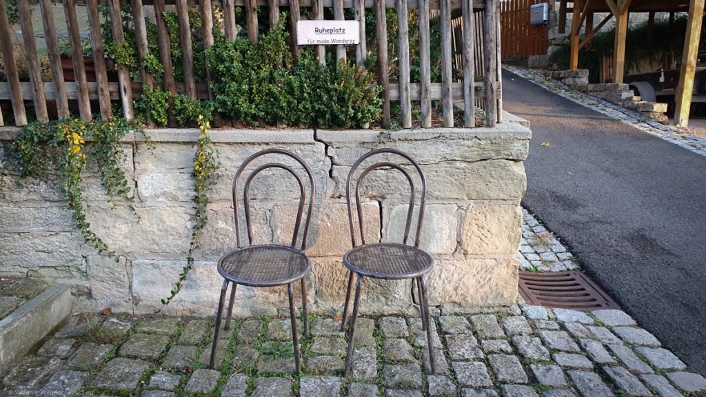 Two metal chairs next to a street