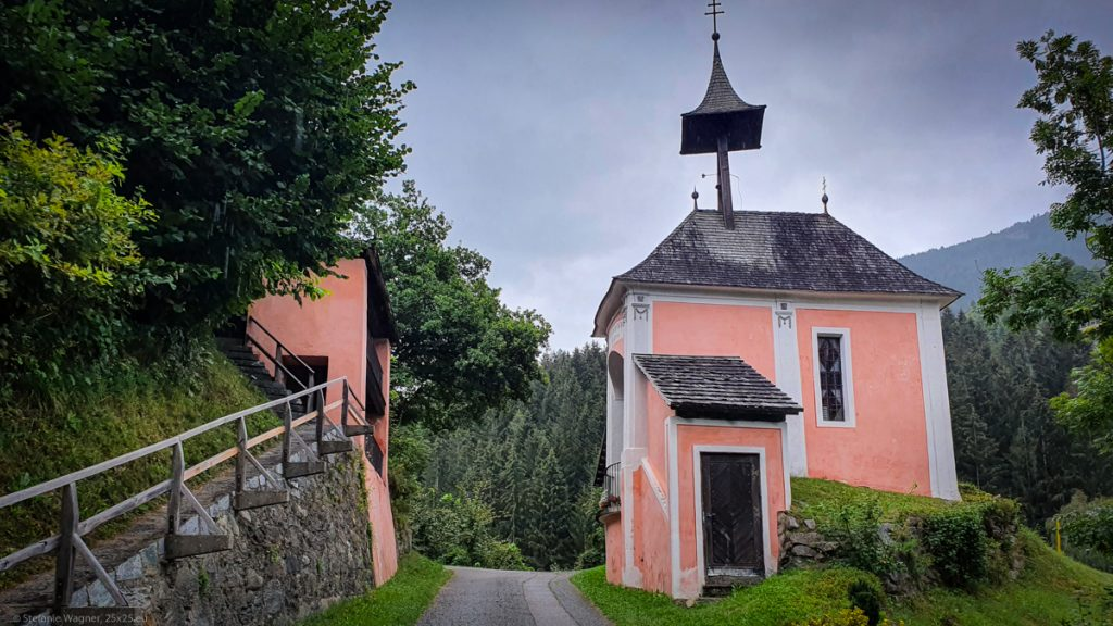Small chapel to the right and a separate small buidling to the left, a street in the middle, buildings painted in pink and white