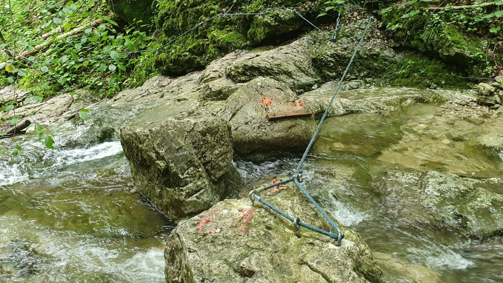Small stream with 3 bigger rocks and a rope across the water next to the rocks, the stones have some red dots