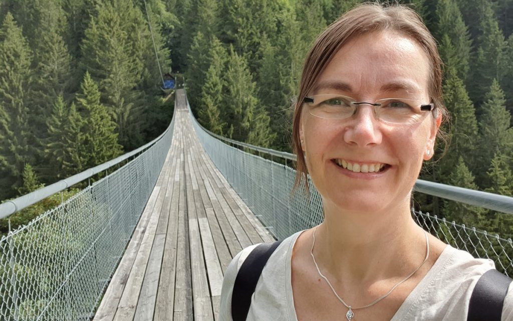Selfie with suspension bridge in the background reaching to the other end of the valley