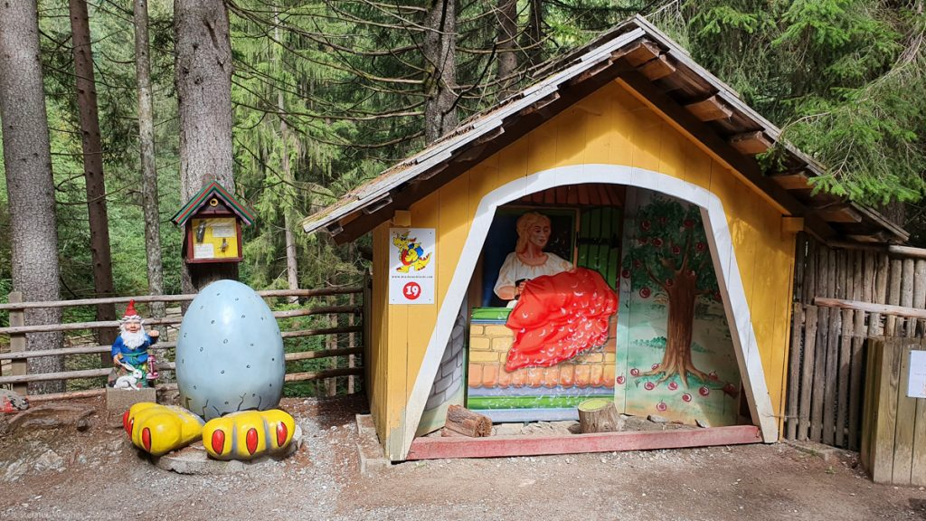 A tiny house showing Mother Hulda, next to it a dwarf, and a giant egg with big yellow feet below it