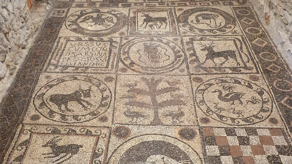 A mosaic flor with 4 rows and 3 columns, mostly pictures of animals but also one with writing and one with a chess pattern