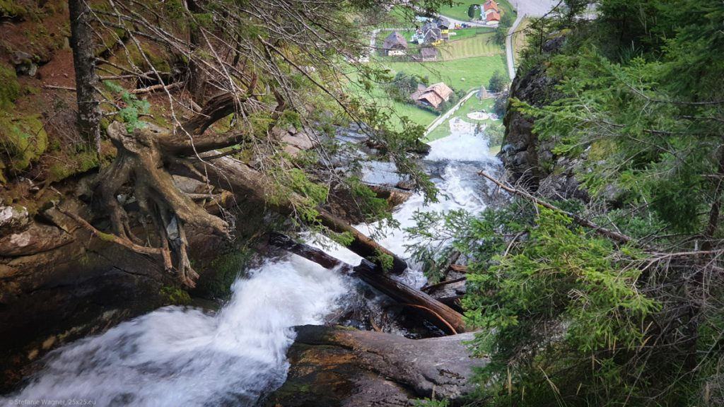 Stream going over an edge, in the background small houses