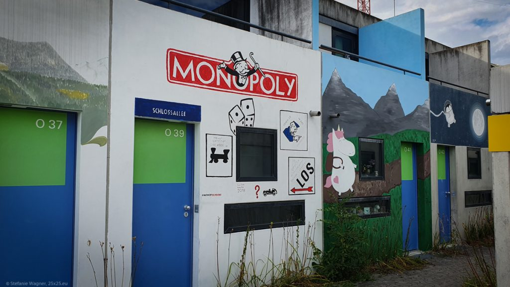 Small house showing the cover of the boardgame Monopoly, next to it a house with a unicorn in a mountain setting hiking