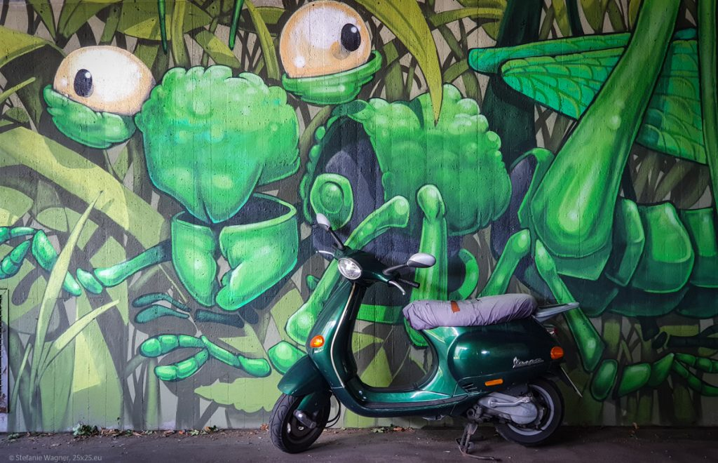 An exaggerated green grasshopper with a green (real life) scooter in front of it
