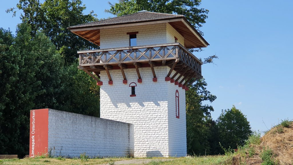"""A three floor watch tower with a wooden balcony on the third floor, white with """"fake"""" stones"""