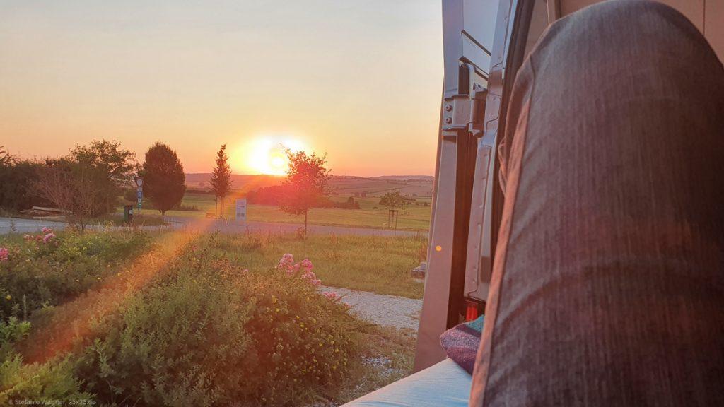 Sunset, view through the open doors of a camper van