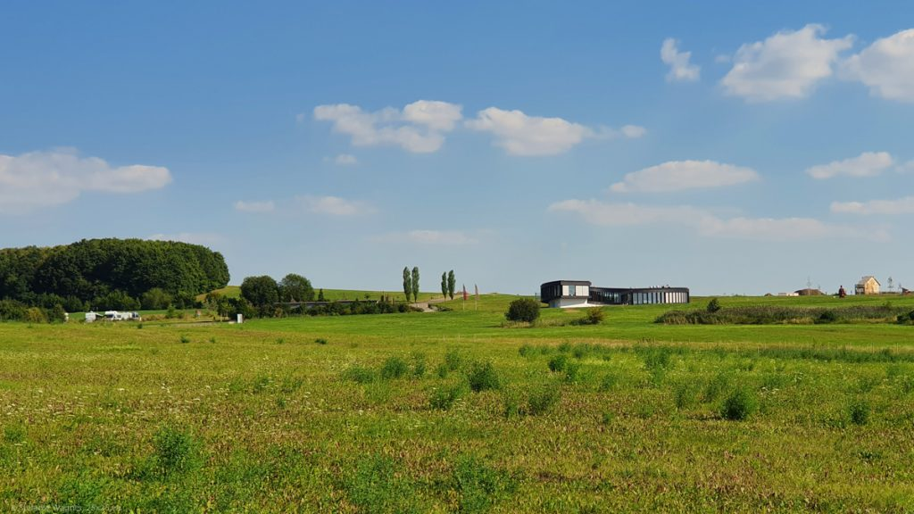 Areal view, lot of green grass, in the background a one floor museum building