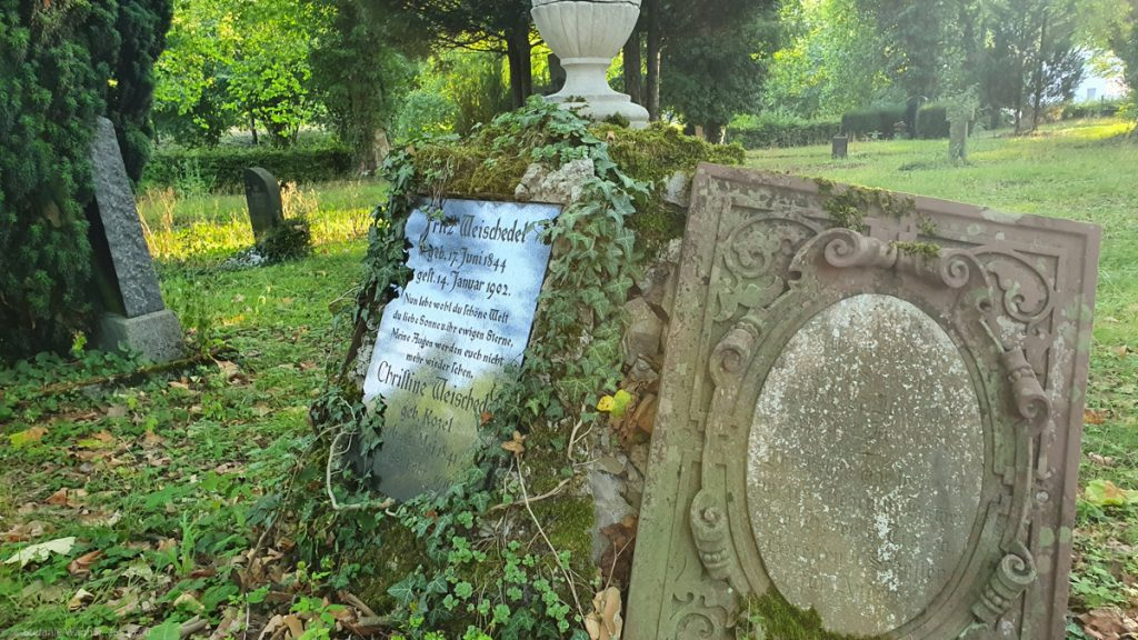 Two old tombstones, the left one looks like it is tipping; death date from 1902