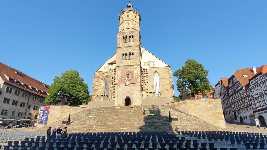 Church on a small hill with a wide staircase leading towards it, a lot of chaires on the square in front of it