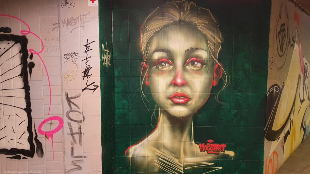Graffiti, green background, white female face and neck, red eyelids, ears, nose and lips, looking with big eyes slightly to the left