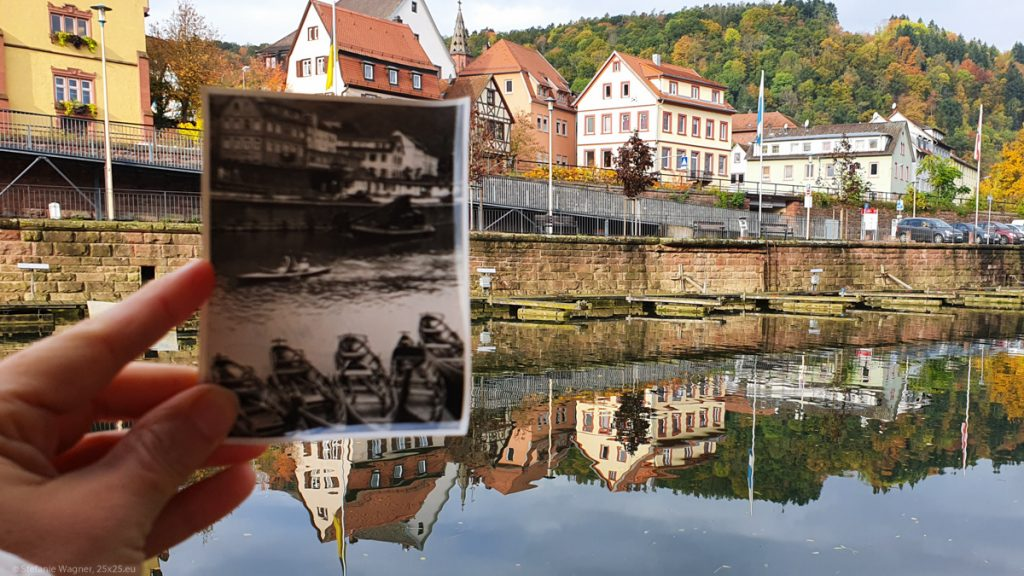 River and houses, a hand holding a picture in the foreground showing part of the scenery