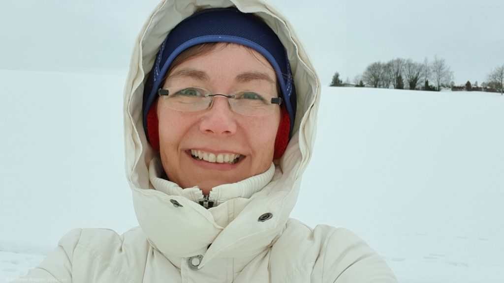 Selfie with thick winter jacket. caps and earmuffs, lot of snow in the background
