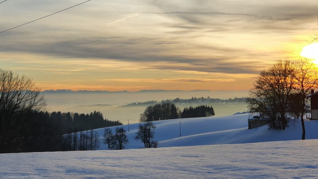 Sunset, view across the snow into the lowlands covered with fog, the outline of the Alps visible at the horizon