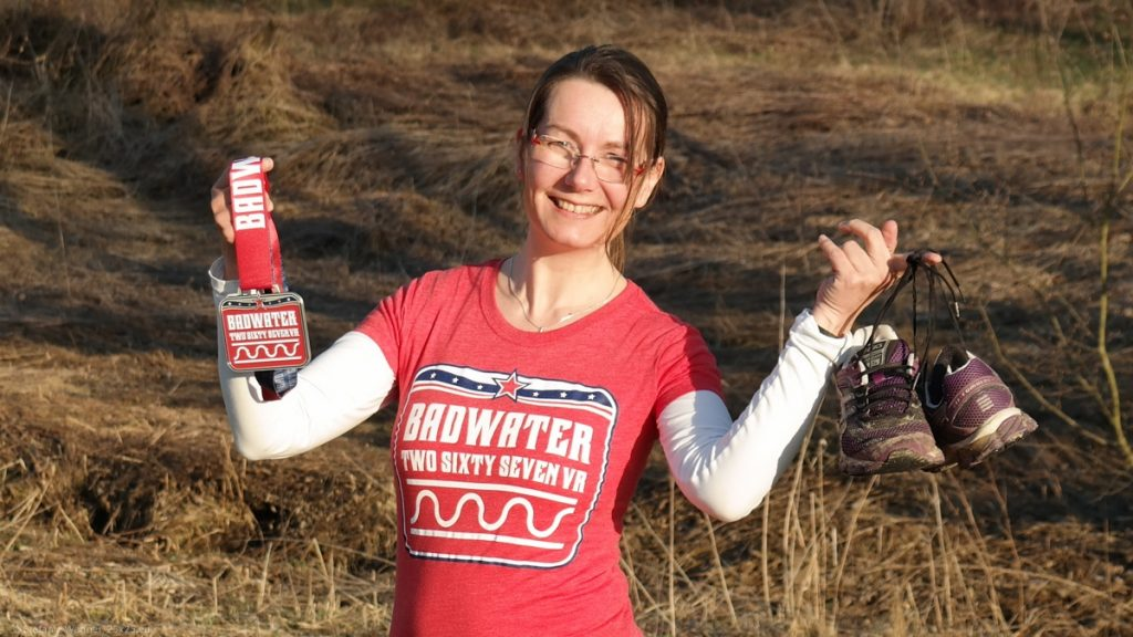"""Red t-shirt with the text """"Badwater Two sixty seven vr"""", a medal of the size of a hand with the same text, running shows"""