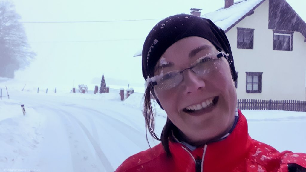 Selfie running during snow - wet/snowy glasses, snow on jacket and cap, street covered with snow in the background