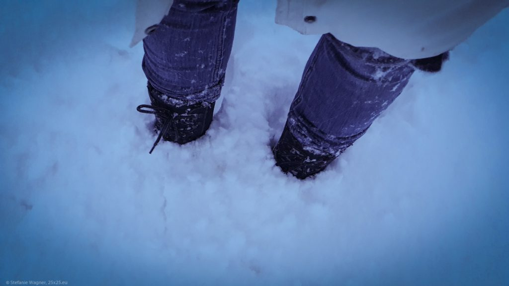 Snow boots half stuck in snow