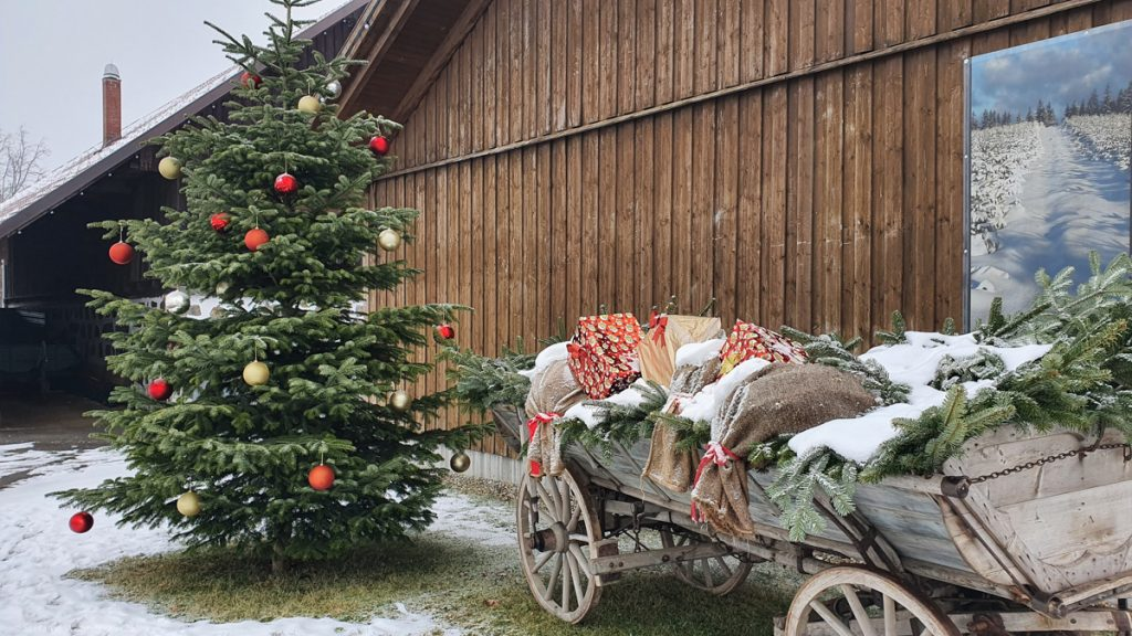 Christmas tree, old carriage with fir branches, wrapped gifts and brown bags