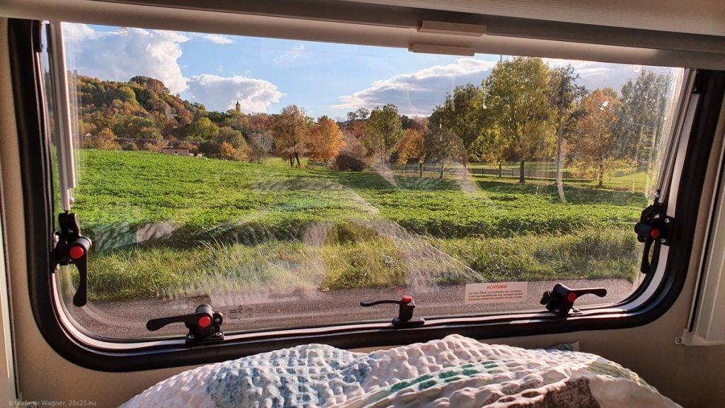 Camper van window: Green field, trees in with colorful leaves, almost blue sky
