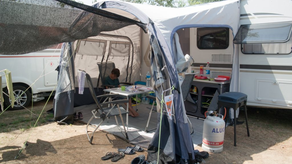 Caravan with awning, under the awning: table, 3 chairs (one with a kid), small storage rack, gas cooker.