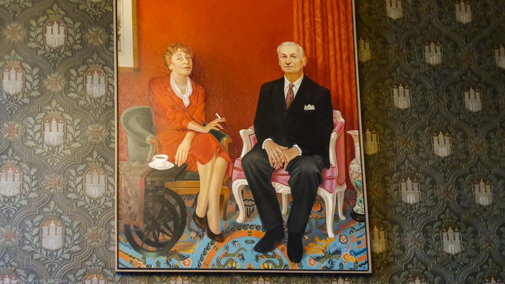Picture of Herbert and Elsbeth Weichmann, red background, she is wearing a red dress almost the same color. He sits on a purple (female) chair, she is sitting on a dark (male) on.