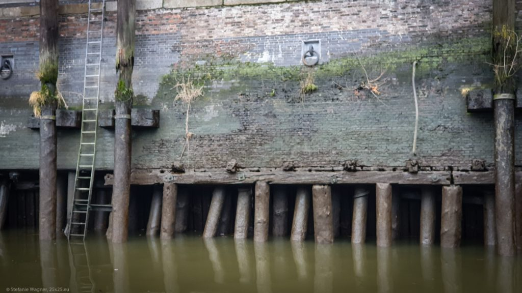 A big wall carried by logs which peek out of the water