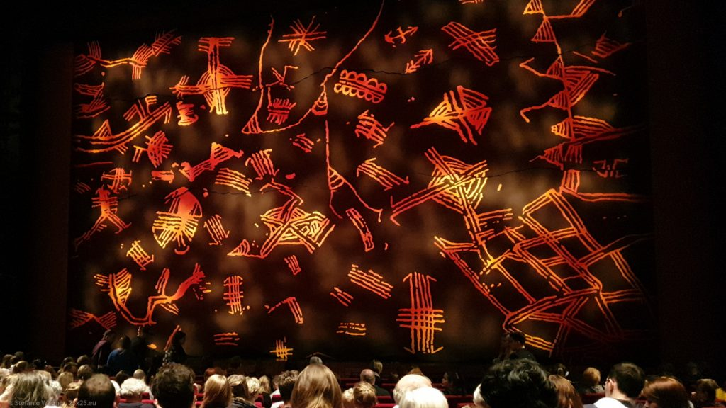 Closed stage curtain with reddish-orange symbols on it