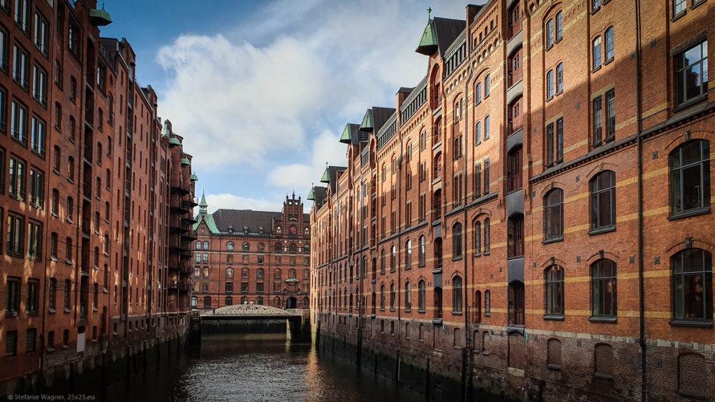 Brown brick buildings with multiple stories, in between water