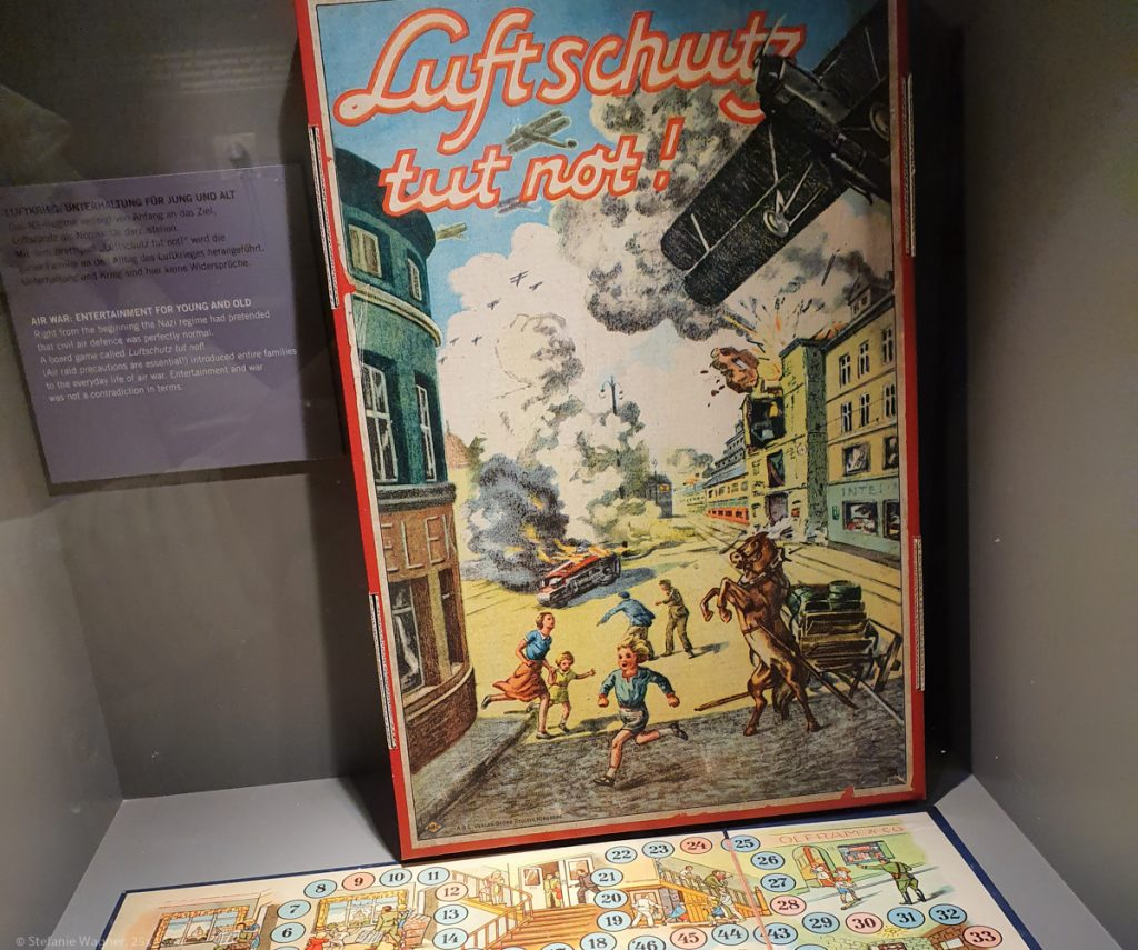 """Cover of a board game saying """"Luftschutz tut not"""" showing a plane bombing houses, a burning car and people running."""