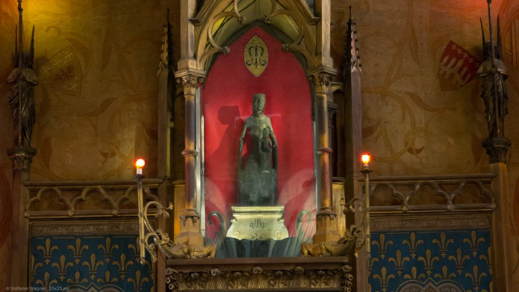 statue of a black madonna with a child behind glass in the church