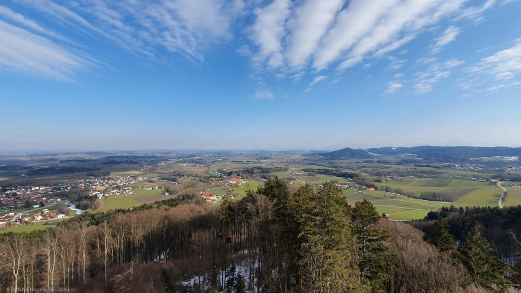 View from the tower, some houses, trees, fields, blue sky with some clouds
