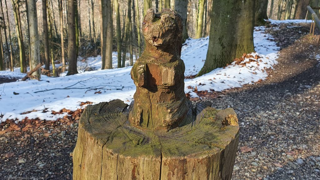 Stump with a small figure of an animal resembling a squirrel on top of it that was carved directly out of the stump