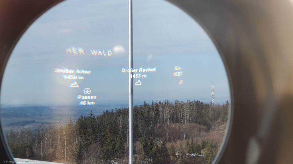 View through a telescope showing the hill with the trees and the landscape in the background in original size, overlaying it with text: Passau, 46 km, Großer Rachel, 1453 m, Großer Arber, 1456m