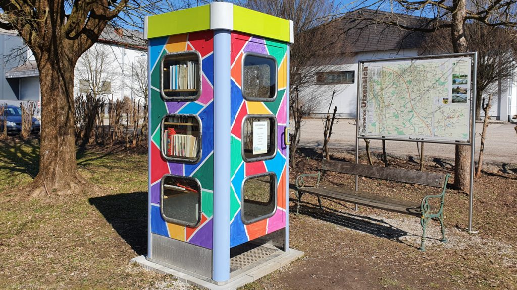 A phone boot painted with green, blue, yellow, orange, pink rectangles. Books visible through the windows.